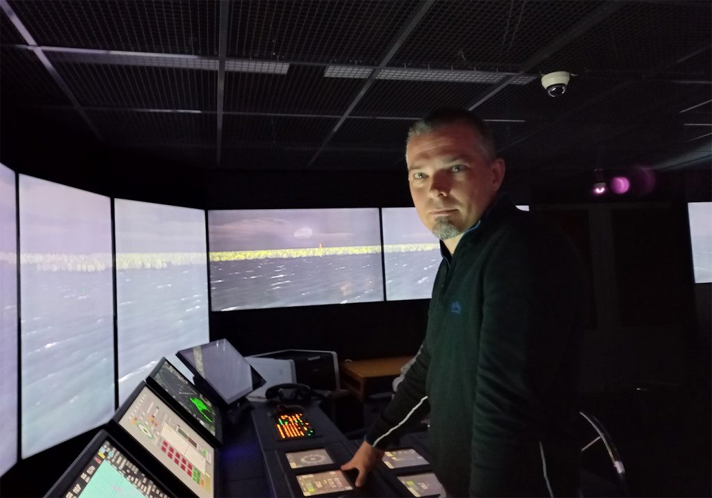 Man standing front of screens in maritime simulator.